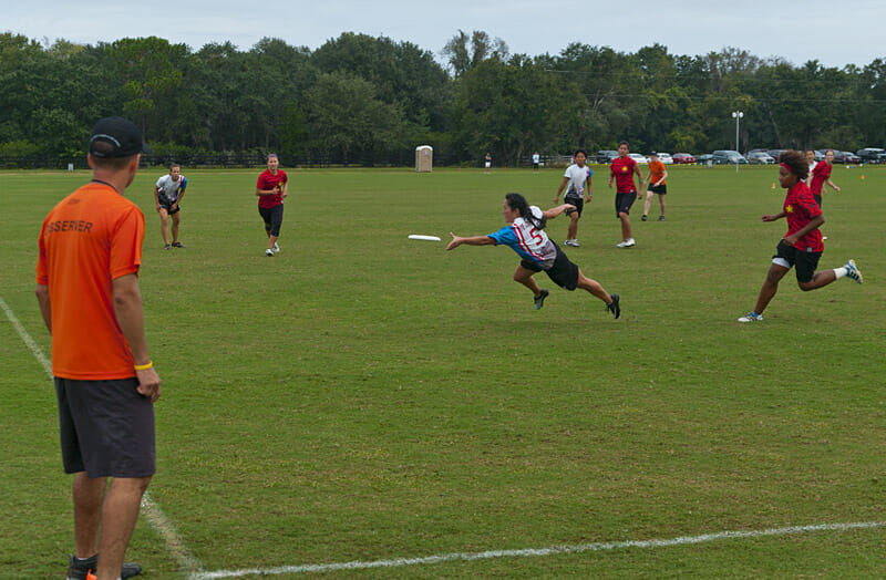 A USA Ultimate observer looks on as a player dives to catch the disc.