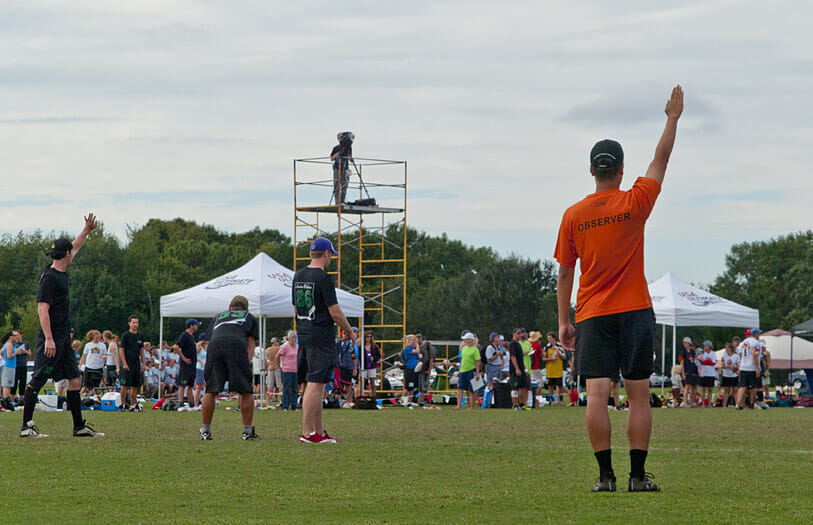 An observer signals readiness as Ultimate players prepare to receive the pull. A cameraman on scaffolding is filming in the background.