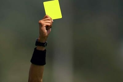 Yellow card being held up by a referee.
