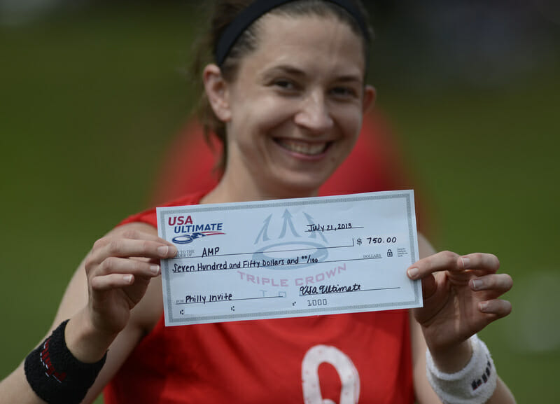 An AMP player shows off the team's prize money for winning the Mixed Pro-Elite Challenge.