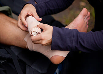 An athletic trainer wraps an ankle.