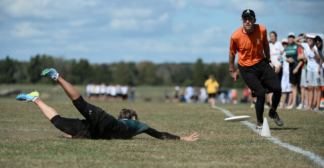 Observer watches as a player dives for a disc.