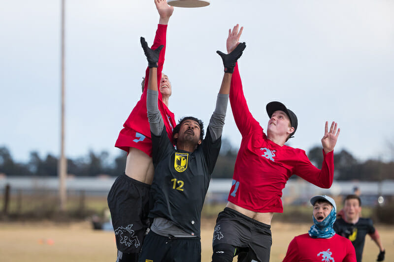 Two Wisconsin players attack a disc in the air against Colorado at the 2018 Stanford Invite.