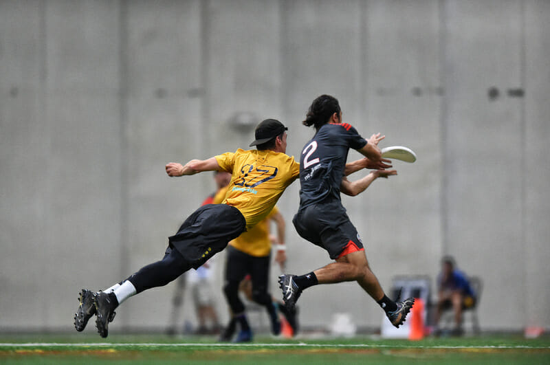 Revolver's Sawyer Thompson gets a layout block against Colony's Peter Eley in the WUCC 2018 final.