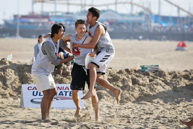 Players celebrate a win during u20 bracket play at the Beach of Dreams event. Photo: Kristina Geddert -- UltiPhotos.com
