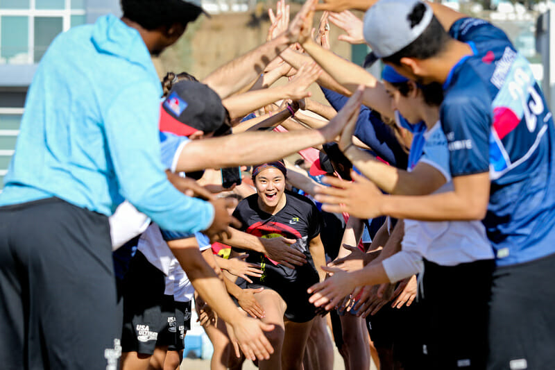 A youth player runs through a tunnel of Live Ultimate ambassadors at the Beach of Dreams event. Photo: Kristina Geddert -- UltiPhotos.com