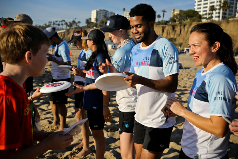 Live Ultimate ambassadors sign discs for youth players at the Beach of Dreams event. Photo: Kristina Geddert -- UltiPhotos.com