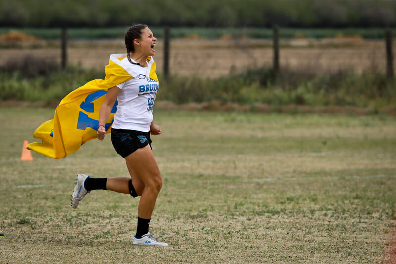 UCLA's Olivia Sandom rushes the field in celebration with a school flag at Stanford Invite 2020. Photo: Kristina Geddert -- UltiPhotos.com