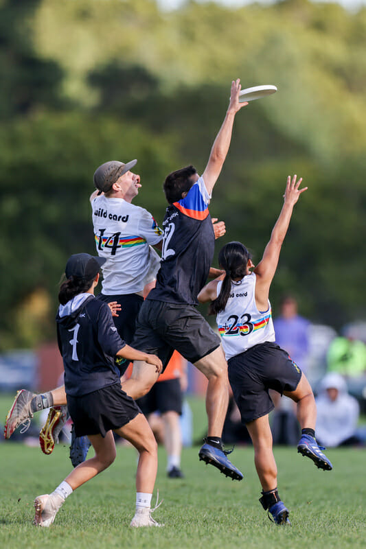 New York XIST wins the disc while being sandwich between two Wild Card players at 2021 Northeast Mixed Club Regionals. Photo: Alec Zabrecky — UltiPhotos.com